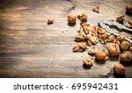 shelled walnuts. on a wooden... | Shutterstock . vector #695942431