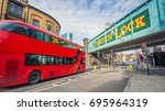 Small photo of London, England - Iconic red double decker bus on the move at the world famous stables market of Camden Town at daylight