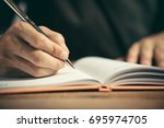 male hand with pen writing in... | Shutterstock . vector #695974705
