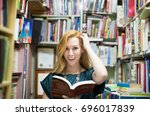 woman surrounded by books.... | Shutterstock . vector #696017839