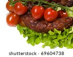 Small photo of Detail of smoked sausage with lettuce and cherry tomato cluster on white background, horizontal orientation in studio shot. Polish kie?basa w?dzona.