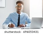 Small photo of People, business, work, job, occupation and profession concept. Attractive positive hardworking young Afro-American office worker sitting at desk in front of open laptop pc and making notes