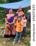 Small photo of North Vietnamese women in colorful native clothing with children in Western garb at Bac Ha market on Oct 23, 2011