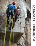 Small photo of Two climbers work on the route entrenched on a rocky ledge. Tilt-Shift effect.