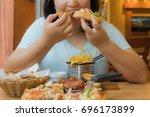 overweight woman is eating... | Shutterstock . vector #696173899