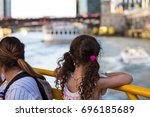 Small photo of Chicago, IL, August 12, 2017: A young girl in pigtails leans over the bar of the Wendella water taxi in Chicago and enjoys the view of the city's beautiful bridges and boats, blurred behind her.