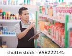 asian male shopkeeper working... | Shutterstock . vector #696222145