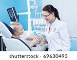 Dentist gives the patient a toothbrush and toothpaste - stock photo