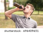 young man drinking a beer in... | Shutterstock . vector #696409651