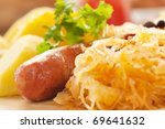 Sausage with potatoes and sauerkraut and bread loaves - stock photo