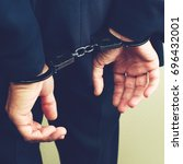 Small photo of arrested businessman in handcuffs. Businessman bribetaker or briber, toned image. Concept of fraud, detention, crime and bribery