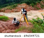 Small photo of Geodetic works on gold mining exploration in Guyana. Two man works with 3D scanner. 3D scanner on tripod, rugged tablet in hands. Jungle, clay and white quartz stones on background.