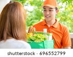 asian delivery man delivering... | Shutterstock . vector #696552799