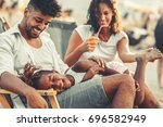 young mixed race family sitting ... | Shutterstock . vector #696582949