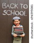 a little boy is holding a pile...   Shutterstock . vector #696595081