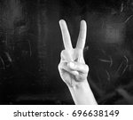 Small photo of Hand on black background fingerspelling the letter V in sign language .