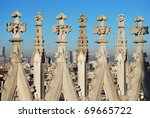 Duomo gothic cathedral of Milan, spires decoration detail, panorama in background, Lombardy, Italy - stock photo