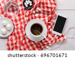 Small photo of Coffee break at restaurant. Porcelain cup of black coffee, lump sugar and smartphone with earphones on checkered tablecloth at white wooden background, top view, copy space