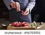 man sprinkles filet mignon... | Shutterstock . vector #696703501