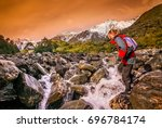 female trekker crossing the... | Shutterstock . vector #696784174