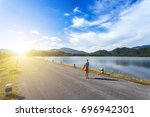 Beautiful woman standing take photograph on asphalt road and blue sky in the background. Happy young woman in a brown hat. Reservoir with mountain in Nakornnayok,Thailand.