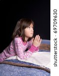 A young girl says her prayers just before bed time. - stock photo