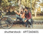 young couple sitting outdoors... | Shutterstock . vector #697260601