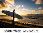 sun sets as a surfer looks at... | Shutterstock . vector #697265071