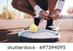 tennis player tying sport shoes.... | Shutterstock . vector #697394095