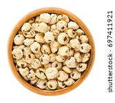 tiger nuts in wooden bowl.... | Shutterstock . vector #697411921