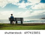 girl sitting on park bench... | Shutterstock . vector #697415851