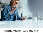 young female executive working... | Shutterstock . vector #697487419