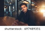 male manufacturer sitting at... | Shutterstock . vector #697489351