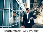 business traveler checking time ... | Shutterstock . vector #697490509