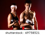 strong young couple working out with dumbbells. Shot in studio on a red background. - stock photo