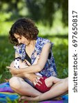 young beautiful mother sits on... | Shutterstock . vector #697650817