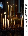 burning candles on standard in... | Shutterstock . vector #697674241