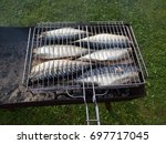 a fish. grilled on charcoal. in ... | Shutterstock . vector #697717045