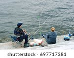 the couple sitting on the pier... | Shutterstock . vector #697717381