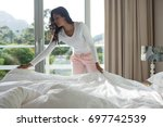 young woman making bed at home | Shutterstock . vector #697742539