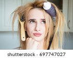 young girl trying to comb her...   Shutterstock . vector #697747027