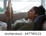 young woman reading book while... | Shutterstock . vector #697785121