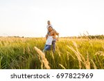 happy family playing in a wheat ... | Shutterstock . vector #697822969
