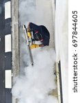 Small photo of Worker fogging residential area to control Aedes mosquito