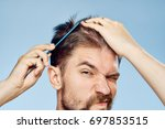 Man Combs His Hair Comb On A...