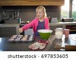 Smiling Girl Pouring Cupcake...