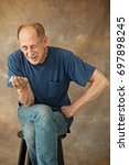worried mature man sitting at...   Shutterstock . vector #697898245