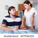 serious couple sitting at desk... | Shutterstock . vector #697946101