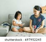 asian little girl and mother... | Shutterstock . vector #697952245