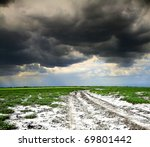 old rural road and dark storm clouds - stock photo